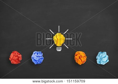 Idea concept crumpled paper light bulb metaphor for good idea on blackboard