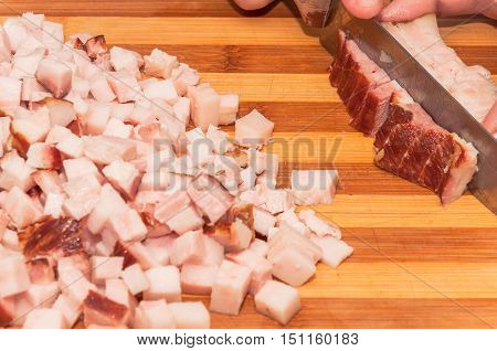 Cutting larger pieces of bacon into small cubes.