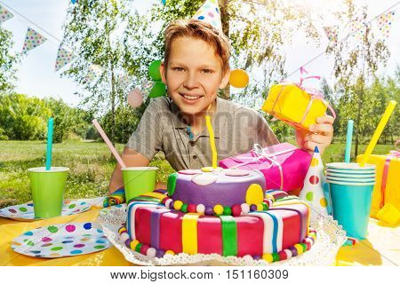 Portrait of happy smiling boy with birthday gifts, sitting next to the birthday cake at the outdoor party