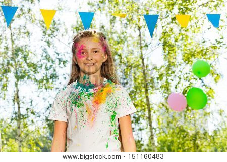 Portrait of young girl covered with colored powder at the outdoor festival