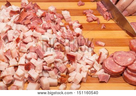 Italian sausage and bacon cut into small pieces on wooden board. Ingredients for preparing a pasta with bacon and Italian sausage.