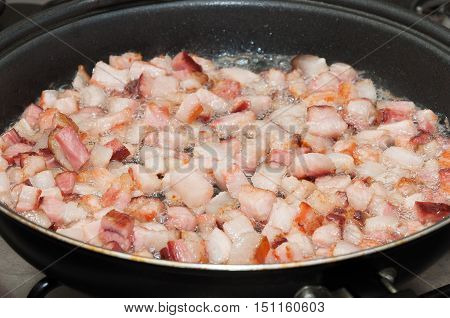 Frying bacon pieces in a pan with hot oil. Preparing ingredients to make a dish. Bacon starting to fry.
