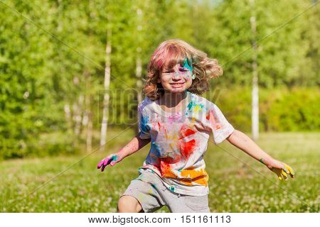 Bright and funny little boy playing with colored powder outside