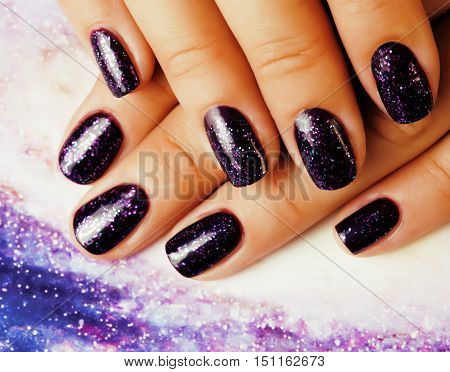 manicure stylish concept: woman fingers with nails purple glitter on nails like cosmos, universe background