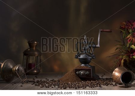 Coffee grinder still life against the backdrop of the fireplace, candle copper, coffee maker