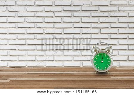 old steel alarm clock on wood floor with and white brick wall lunch time interior vintage background