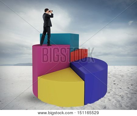Businessman looks at the economic future with binoculars over a graph