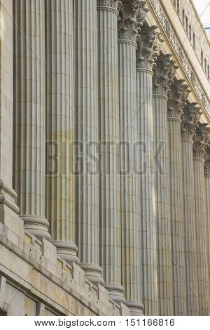 Tall stone corinthian columns in front of large city building