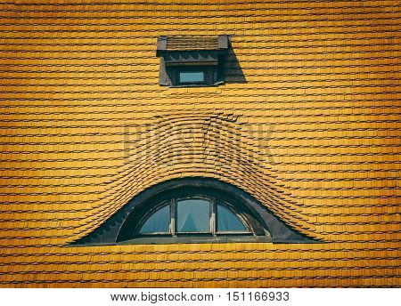 Two dormer windows of the old house with a tiled roof