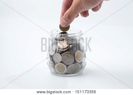 Man drops money into a glass jar for a savings account.