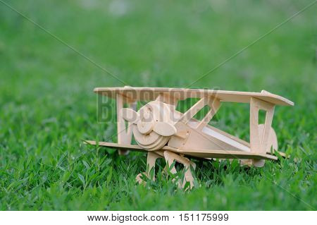 Closeup wooden plane toy on grass floor background