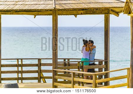 SALINAS, ECUADOR, OCTOBER - 2015 - Young couple kissing at La chocolatera a famous nature viewpoint towars the pacific ocean located at rocky coast in Salinas Ecuador