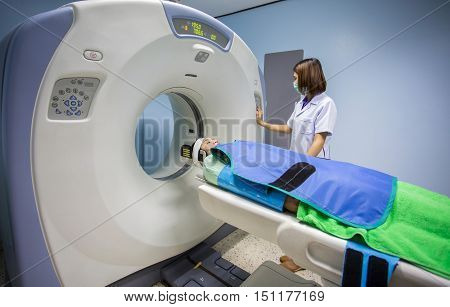 Radiologic technician mature female patient lying on a CT Scan bed