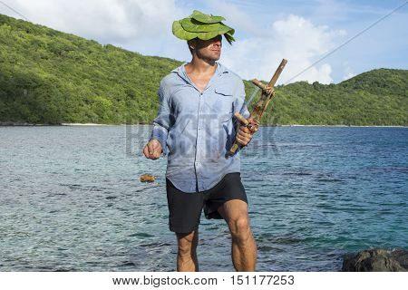 Caucasian male castaway wearing dirty wet clothes and sea grapes hat holds wooden fishing tool while gazing toward the sun on tropical island