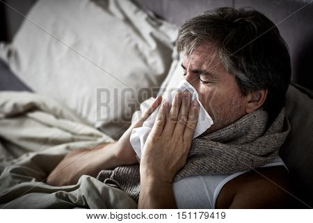 Sick man with cold lying in bed and blow nose.