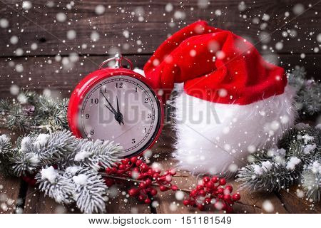 Vintage red clock Santa hat branches fur tree and red berries on aged wooden background. Selective focus. Drawn snow.