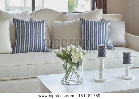 Blue Striped Pillows On A Casual Sofa And Decorative Flower In Glass Vase In Living Room