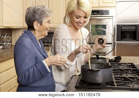Elderly Woman Cooking with her Granddaughter in the kitchen.  They are stirring something in a pot and are smiling.
