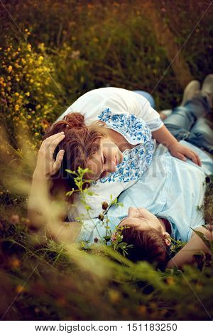 Loving couple lying in the grass in a summer field. A man and a pregnant woman full with love looking at each other
