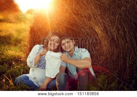 Happy couple expecting a baby sitting on the field near the haystacks and keep a small bodysuit together. In the evening at sunset the husband and pregnant wife have a rest on the nature