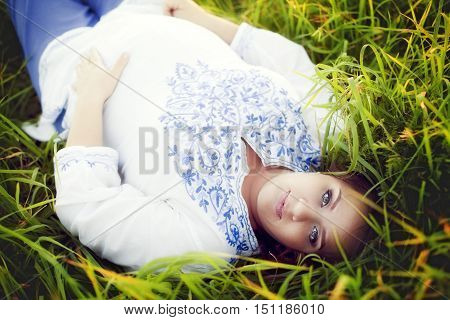 European beautiful pregnant woman in the summer lies on green grass and looking directly at the camera supports abdomen with hands. Girl in folk costume