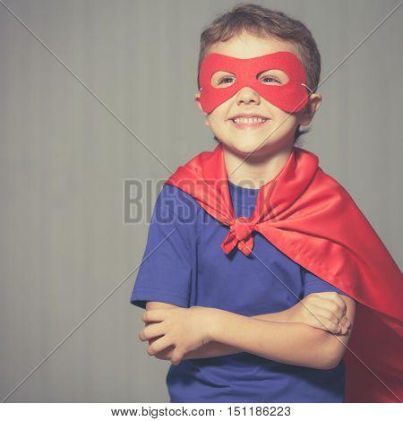 Happy little child playing superhero. Kid having fun outdoors. Concept of boy power.