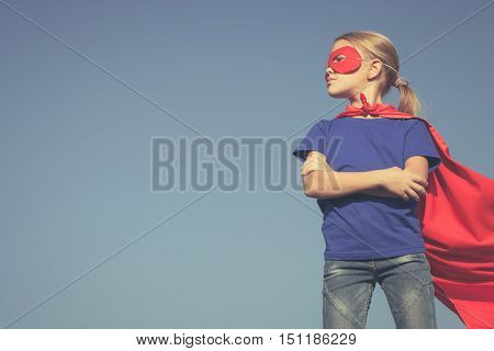 Happy little child playing superhero. Kid having fun outdoors. Concept of girl power.