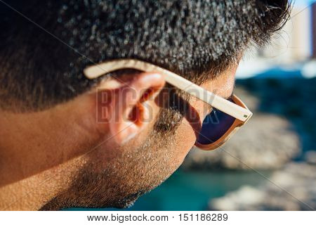 Over shoulder view of sunglasses on stylish brunet man