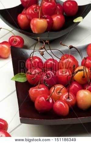Arrangement Fresh Ripe Sweet Maraschino Cherries on Black Wooden Plates Cross Section on Plank White background. Focus on Foreground