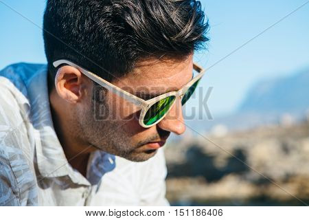 Portrait of stylish sad man with sunglasses looking down outdoors