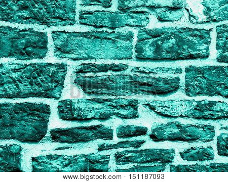 Background of Turquoise Wall Stones with Cracked Surface and Concrete closeup Outdoors