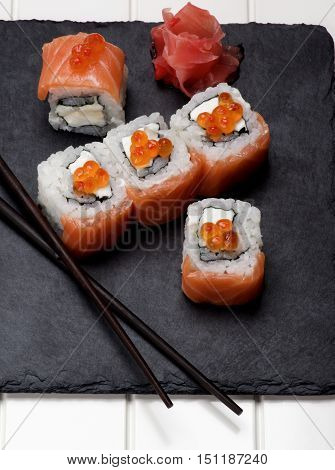 Delicious Sushi with Smoked Sliced Salmon and Gourmet Red Caviar and Ginger on Stone Plate with Chopsticks with Shadows closeup on White Plank background