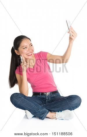 Full body young Asian girl in pink shirt taking self photo or selfie with smartphone, seated on floor, full length isolated on white background.