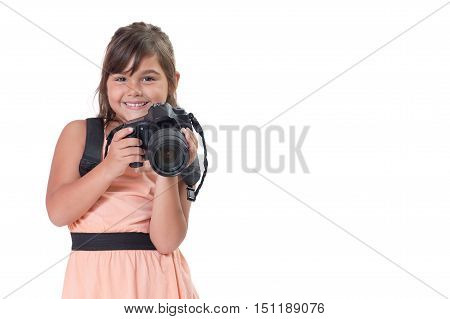 Smiling long hair little girl is holding SLR camera. All is isolated on the white background. All potential trademarks are removed.