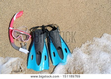 Beach vacation activity: snorkel equipment for women. Scuba diving and snorkelling. Blue Flippers, pink mask, snorkel on sandy texture background. Objects lying on sand.