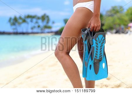 Closeup of sexy legs of bikini woman with snorkeling equipment standing looking at ocean. Girl holding blue flippers ready for snorkel. Scuba diving beach vacation concept.