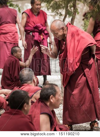 LHASA, TIBET-MAY 2016: A senior monk debates with his fellows in Sera monastery, Lhasa, Tibet. Tibetan monk debate happens daily in the monastery's courtyard. Monk debate is open to the public.