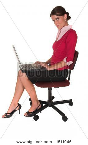 Professional Young White Lady Sitting In Office Chair Typing On Notebook/ Laptop, Red Sweater And Bl