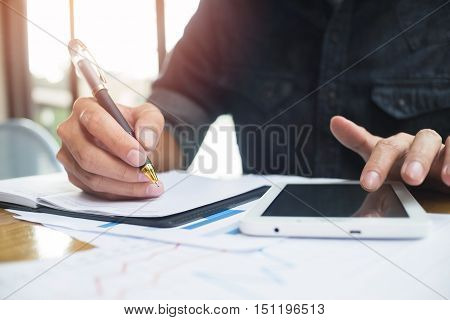 Businessman using a tablet pc and write something.