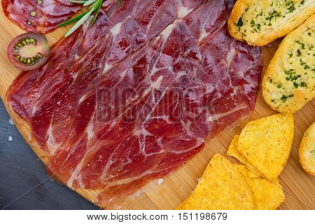 Plate with spanish jamon ham and chorizo tapas, picnic table