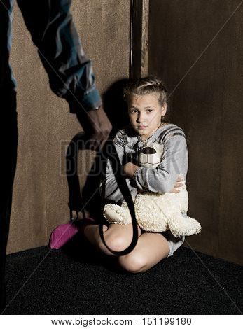 Sad little girl sitting against the wall in despair. In his hands he holds an teddy bear. Angry man threatens with belt