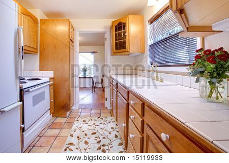 Oak Cabinets Kitchen With Tile Floor And Flowers