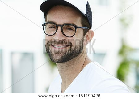 Confident man smiling and wearing glasses in town