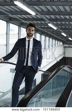 Cool businessman on escalator portrait wearing a suit