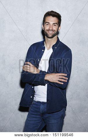 Confident man in blue fashion smiling - in studio