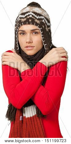 Young woman with a winter hat and a winter scarf rubbing her own shoulders