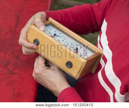 Man is adjusting wooden chess clock red background