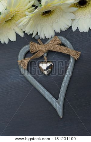 Beige gerbera flowers frame on dark wood with heart close up