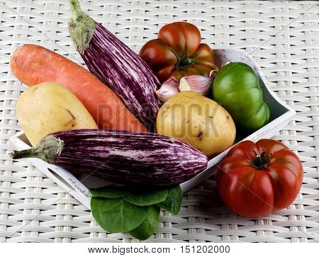 Arrangement of Fresh Raw Vegetables with Striped Eggplants Potato Carrot Green and Red Tomatoes and Garlic on Wooden Tray closeup on Wicker background