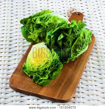 Fresh Crunchy Romaine Lettuce Full Head and Half on Wooden Cutting Board closeup on Wicker background